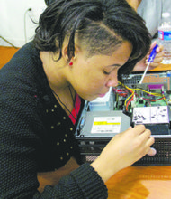 Troi Fox, 14, takes a computer apart during the March 8 session of the EMPOwERgirlz Mentoring Program at the YWCA in Northwest. (Courtesy of Ameena Green)