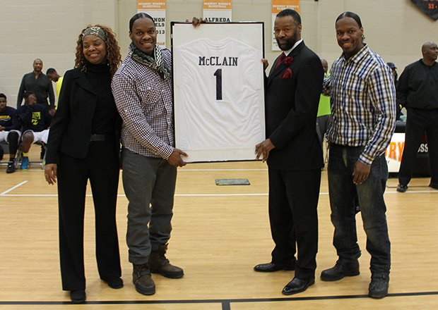 "Al McClain's Hyde Park High School basketball number ""1"" was officially retired at a ceremony at the Reggie Lewis Center in Roxbury. McClain, picture right in suit, played college basketball at the University of New Hampshire, where he still holds the scoring record. He was later drafted by the Houston Rockets. Also pictured are McClain's sister Almand and twin brothers Billy and Bobby who are professional dancers known as The Wonder Twins."