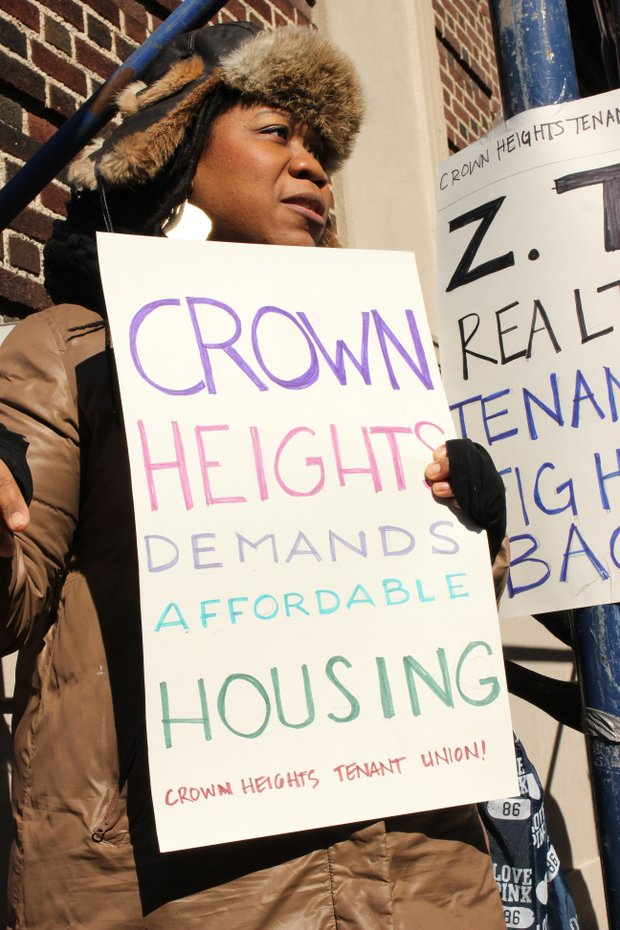 Protestor representing the Crown Heights Tenant Union at a rally for better treatment and affordable housing from landlords.