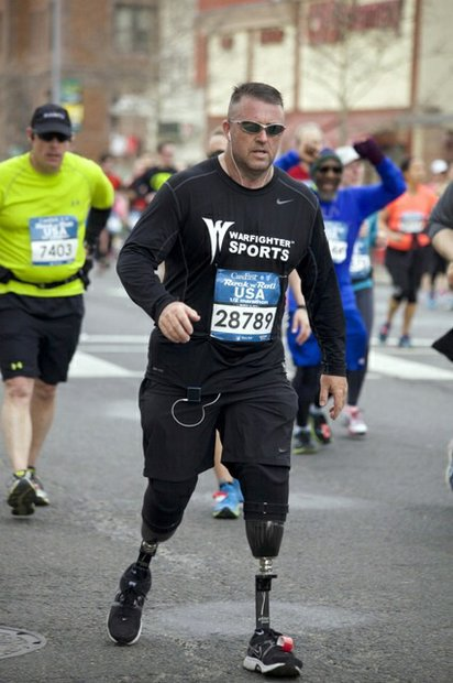 Military veteran Stephen Martin, running on two prosthetic legs, participates in the half-marathon version of the D.C. Rock 'n' Roll Marathon in Northwest on March 15, 2014. Martin wears a shirt representing Warfighter Sports, a national program that offers sports rehabilitation programs in military hospitals and communities.