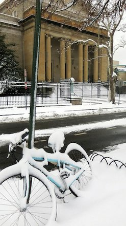 A bicycle chained to a street sign sits in front of the Christian Science Church in D.C.'s Adams Morgan neighborhood on March 17, 2014, after a winter storm hit the region.