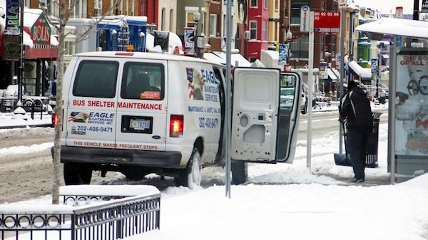 Bus shelter maintenance workers in D.C. remove snow and ice on March 17, 2014, after a winter storm hit the region.