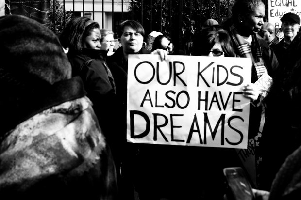 "A sign reads, ""Our Kids Also Have Dreams."" Photo by Keiffer Jordan."
