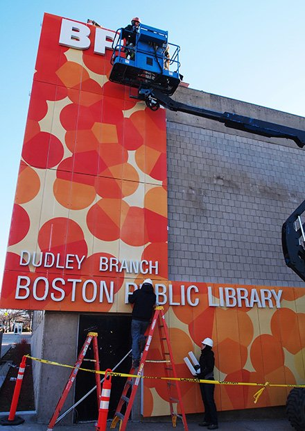 A new look for the Dudley Library: Workers install lettering on the side of the Dudley Branch of the Boston Public Library's new façade. The new design will be backlit with luminous lettering.