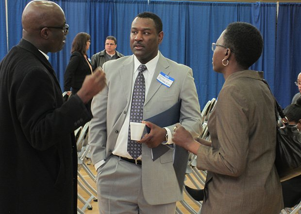 "Daniel Skerrit, center, owner of the Somerville-based Pinctada Banquets & Events LLC, talks to other small business owners at the ""Mass. Business Matchmaker"" event this week in Roxbury."