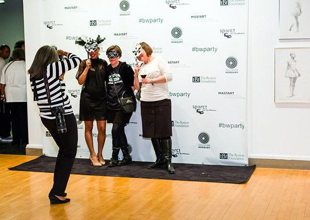 "Photographer capturing guests In front of the ""Step & Repeat"" Banner"