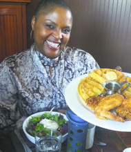 Tanya Holland, co-owner of Brown Sugar Kitchen, with her famous buttermilk fried chicken and cornbread waffles, served with a light brown sugar butter and apple cider syrup, and a fresh, simple side salad.