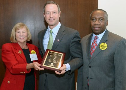 Governor Martin O'Malley receives Lifetime Leadership Award  from Trudy McFall, MAHC president, joined by Maryland Department of Housing and Community Development Secretary Ray Skinner.