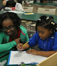 Middle school student and mentor LaTajah Birdsong helps Kaleigh Smith with school work. Through the program, older students mentor and help younger students with various tasks such as homework, reading and general activities.