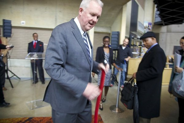 D.C. Council member Tommy Wells removes the rope to let job seekers into the D.C. Job Fair on March 28 at the Mead Center for American Theater in Southwest.