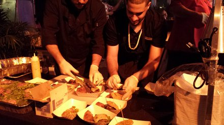Staff prepares plates of food at the event.