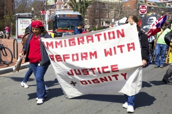 Two participants in a rally in D.C. for immigrant rights hold a sign while marching from Mount Pleasant Street NW to the White House on April 5, 2014.