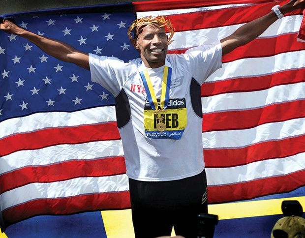 Meb Keflezighi of San Diego, the first American man o win the Boston Marathon since 1983, cloaks himself in the American flag to celebrate.