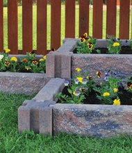 Incorporating raised flower beds using stone planters can beautify the landscape without taking a lot of time or effort.