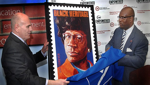 """Boston  Postmaster James J. Holland (l) and Urban League of Eastern Massachusetts CEO Darnell Williams (r) unveil the new Shirley Chisholm Black Heritage """"Forever"""" stamp at the Roxbury headquarters of the Urban League."""
