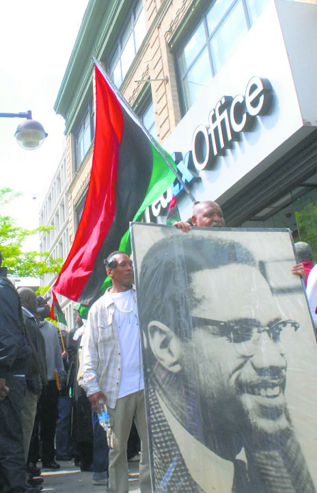 Dozens of people celebrating what would have been Malcolm X's 89th birthday stood beneath a hoisted red, black and green ...