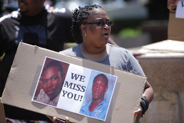 A woman holds a poster displaying the photos of Eric Glover and Terrance Rankins, who were killed in January 2013, in protest of the 10-year sentence one of his murderers received in exchange for her promise to testify against the other defendants.
