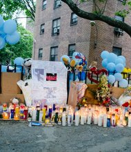 Friends, family, neighbors and well wishers lit candles and posted signs outside the East New York building complex where two children were stabbed. - June 3, 2014