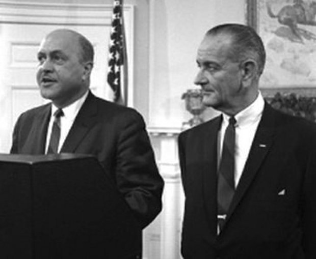Robert C. Weaver standing next to President Lyndon B. Johnson as he is introduced as the