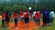 Members of the Georgia Reds youth baseball and Georgia Red Hots kickball teams release balloons on the ballfield at Browns Mill Park on June 7 in memory of their late coach, Pedro A. Sanders.