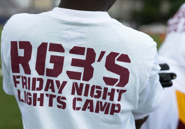 "A young child sports the RGIII Friday Night Lights shirt before the start of Robert Griffin III first-ever ""Friday Night Lights"" football camp at Anacostia Senior High on Friday, June 13. Khalid Naji-Allah"