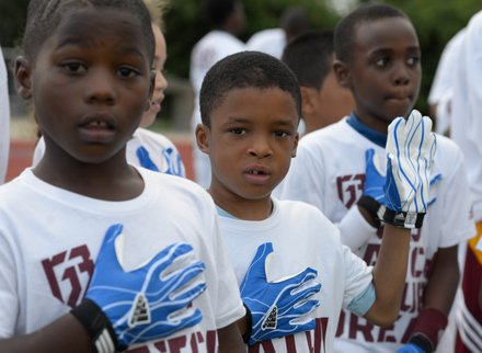 """Camp participants say the Pledge of Allegiance before the start of Robert Griffin III first-ever """"Friday Night Lights"""" football camp at Anacostia Senior High on Friday, June 13."""