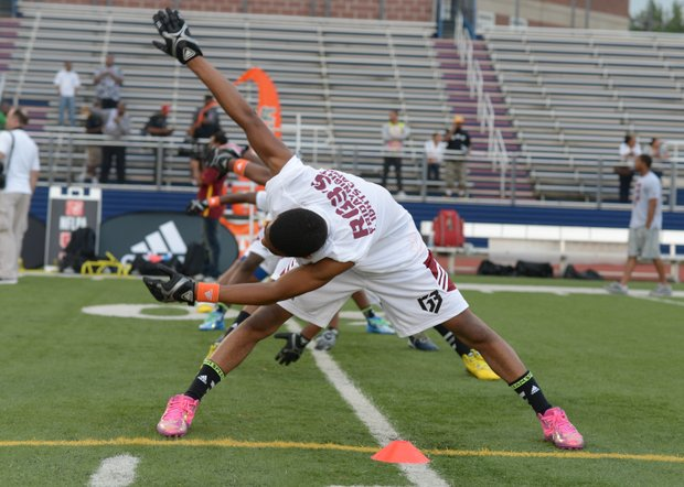 """A camper stretches during Robert Griffin III's first-ever """"Friday Night Lights"""" football camp at Anacostia Senior High on Friday, June 13."""