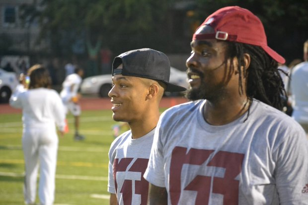 "Rappers Bow Wow (left) and Wale participate in Washington Redskins quarterback Robert Griffin III's ""Friday Nights Lights"" football camp at D.C.'s Anacostia High School on June 13. (Andrew Walker/Washington Redskins)"
