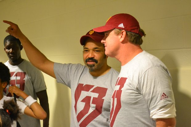 "Actor Jeffrey Wright (left) talks with Washington Redskins head coach Jay Gruden during Robert Griffin III's ""Friday Nights Lights"" football camp at D.C.'s Anacostia High School on June 13. (Andrew Walker/Washington Redskins)"