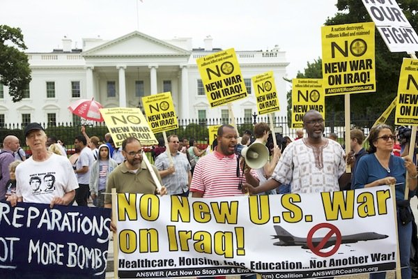 From left: David Barrows, Sunil Freeman, Eugene Puryear (with megaphone), Akufuna Ngonda, and Elizabeth Loweng stand behind banners in front of the White House on June 21 during a demonstration against new military action in Iraq.