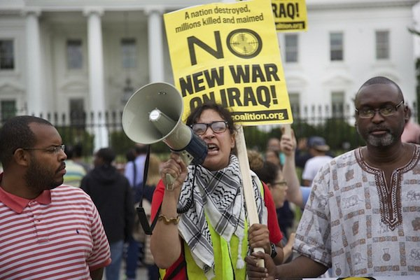Heather Bennom of D.C. speaks through a megaphone in front of the White House on June 21 during a demonstration against new military action in Iraq.