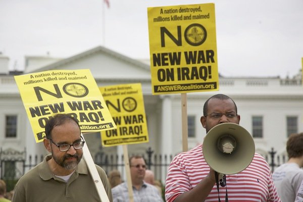 Eugene Puryear (right), a Green Party candidate for an at-large seat on the D.C. Council, speaks through a megaphone in front of the White House on June 21 during a demonstration against new military action in Iraq.