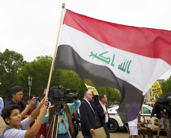 Yassin Allalak, an 11-year-old boy from Iraq, raises the flag of his home nation in front of the White House on June 21 during a demonstration against new military action in Iraq.