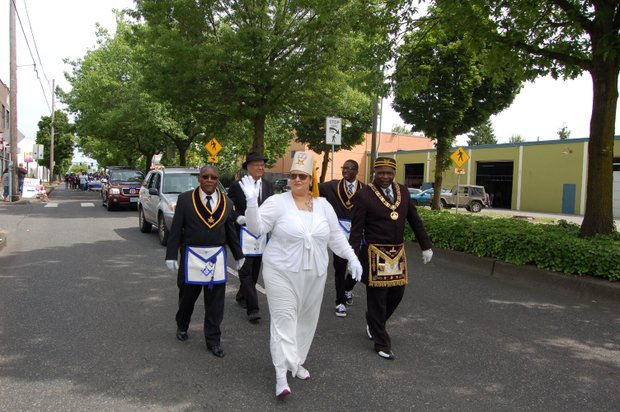 Representatives from the Freemasons and Eastern Stars of the 'Sons of Haiti' Masonic Lodge on North Mississippi Avenue greet spectators at the Juneteenth celebration along Martin Luther King Boulevard.