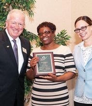 Renee Gillis (center) receives her award from  Arc Baltimore Executive Director Stephen Morgan (left) and Arc Board President Carla N. Murphy (right).