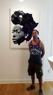 Artist Lobyn Hamilton, a featured artist in Gallery Guichard's Genesis exhibition, seen here with one of his signature broken vinyl works, a black and white drawing of an African American woman with a broken vinyl Afro in the shape of the Continent of Africa.