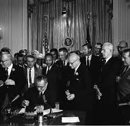 President Lyndon B. Johnson signing the Civil Rights Act of 1964. Martin Luther King, Jr. (behind) observing Johnson signing the act.