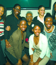 Dr. Muriel Petioni (standing center, rear) surrounded by high school seniors