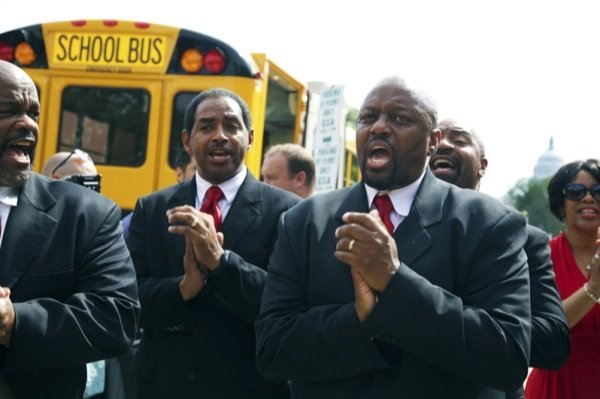 A group named No Chains sings as a bus containing original members of the Freedom Riders heads to Richmond, Virginia, for a June 2 ceremony to commemorate the 50th anniversary of the Civil Rights Act.