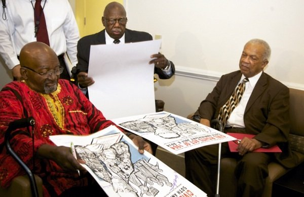 Freedom Riders John Moody, Charles Person and Rev. Reginald Green sign posters during a June 2 ceremony at a U.S. Department of Education facility in Richmond, Virginia, to commemorate the 50th anniversary of the Civil Rights Act.