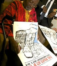 Freedom Rider John Moody signs posters during a June 2 ceremony at a U.S. Department of Education facility in Richmond, Virginia, to commemorate the 50th anniversary of the Civil Rights Act.