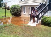 A large puddle of water from broken pipes stands in front of Denise DeBurst Gines' home on Dogwood Farms Road.