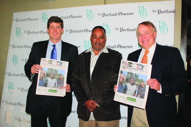 Patrick Quinton (left) and John Jackley of the Portland Development Commission hold up their copies of The Portland Observer, Oregon's oldest minority publication, at the NNPA convention in Portland, with the newspaper's publisher Mark Washington.