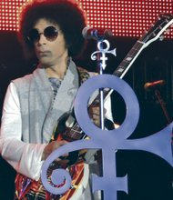 Prince, sporting a short 'fro, rocked the crowd Friday night at the Essence Festival. ( L. Toomer)