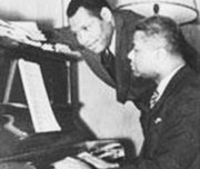 Lawrence Brown at the piano with Paul Robeson looking on