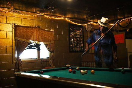 Melvin Williams, 64, plays pool in Odessa's Place, a small one-room bar in the impoverished Baptist Town neighborhood of Greenwood. Odessa Nicks, 85, opened the bar in 1963 and has kept it going in old age so that she remains occupied. Williams pays $200 a month in rent to live in an apartment directly behind the bar. (Edmund D. Fountain, special to ProPublica)