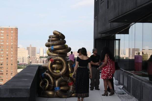 "Scherezade Garcia's ""Cathedral/Catedral"" pile of gold tubes with a rooftop view of Manhattan from the Sugar Hill Apartment on the Corner of 155th Street and St. Nicholas Ave."