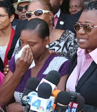 Maisha Allums, the daughter of Marlene Pinnock who was seen being beaten by a California Highway Patrol officer on a viral video, stands with family attorney Caree Harper during a press conference held at the Los Angeles Sentinel office on July 10, 2014. (Nicole Williams)