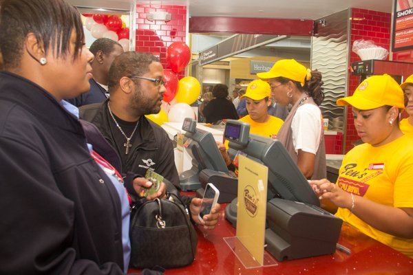 Camille Palmer (left) and Alan Pauls (right) are the first guests at Ben's Chili Bowl's newest location at National Airport in Arlington, Va., on Wed., July 23.