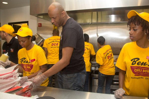 Ben's Chili Bowl employees serve up chili dogs during the celebration of the restaurant's newest location at National Airport in Arlington, Va., on Wed., July 23.